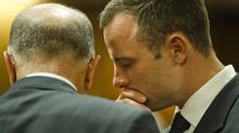 Oscar Pistorius, right, talks with his uncle Arnold Pistorius in court on the fifth day of his trial at the high court in Pretoria, South Africa, Friday, March 7, 2014. (Theana Breugem/AP)
