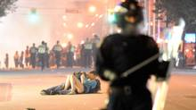 Riot police walk in the street as a couple kiss on June 15, 2011 in Vancouver, Canada. Vancouver broke out in riots after their hockey team the Vancouver Canucks lost in Game Seven of the Stanley Cup Finals. (Rich Lam/Getty Images)