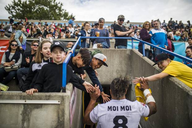 Fans give Toronto Wolfpack player Fui Fui Moi Moi high fives during halftime.