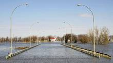The Morris River continues to rise in Morris, Man., and the main bridge into the city on Highway 75 is under water and remains closed off by a dike, Monday April 25, 2011. (David Lipnowski/The Canadian Press)
