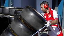 A Ferrari Formula One team member moves tires into the garage at the Albert Park circuit in Melbourne March 14, 2013, ahead of the Australian F1 Grand Prix. (DANIEL MUNOZ/REUTERS)