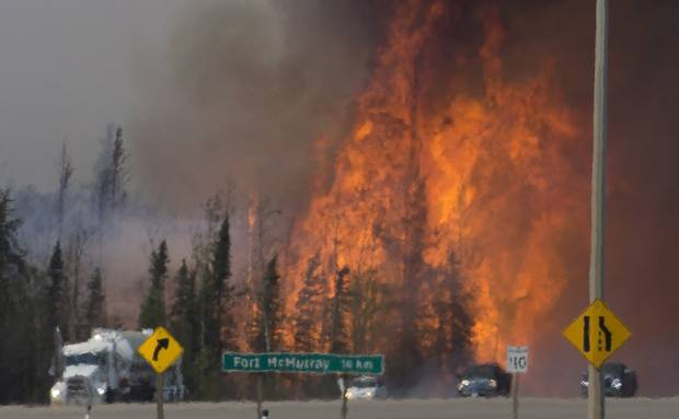 Cars and trucks try and get past a wildfire 16 km south of Fort McMurray last May.
