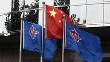 Flags of China National Offshore Oil Corp. (CNOOC) fly beside the China flag in front of its headquarters building last week. (JASON LEE/REUTERS)