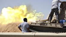 A tank belonging to the Western Shield, a branch of the Libya Shield forces, fires during a clash with rival militias around the former Libyan army camp, Camp 27, in the 27 district, west of Tripoli, Aug. 22. (STRINGER/REUTERS)
