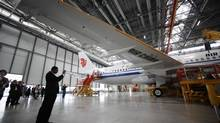 A journalist photographs a A320 plane under construction for Air China Airlines at the Airbus factory in Tianjin municipality, June 13, 2012. China's aviation sector is striving to build its own high-performance jet engine to end its reliance on foreign builders. (JASON LEE/REUTERS)