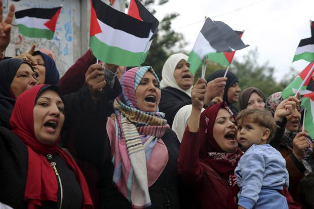 Women wave Palestinian flags and chant slogans during a protest at the Unknown Soldier Square in Gaza City on Dec. 6, 2017.