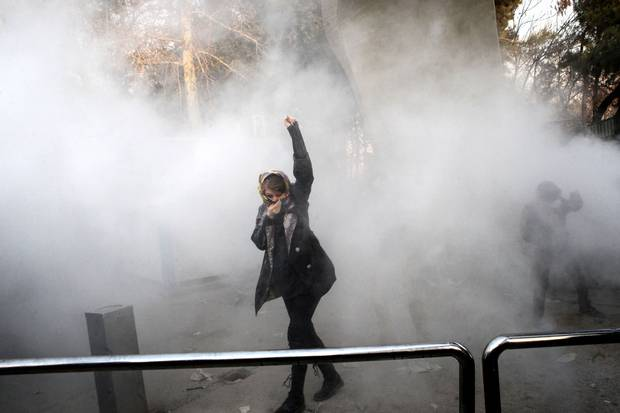 Dec. 30, 2017: An Iranian woman raises her fist amid the smoke of tear gas at the University of Tehran during a protest driven by anger over economic problems.