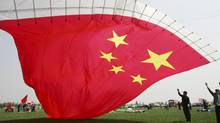 Contestants try to fly a kite featuring Chinese national flag during a kite-flying contest in Weifang, Shandong province, April 17, 2012. (REUTERS)