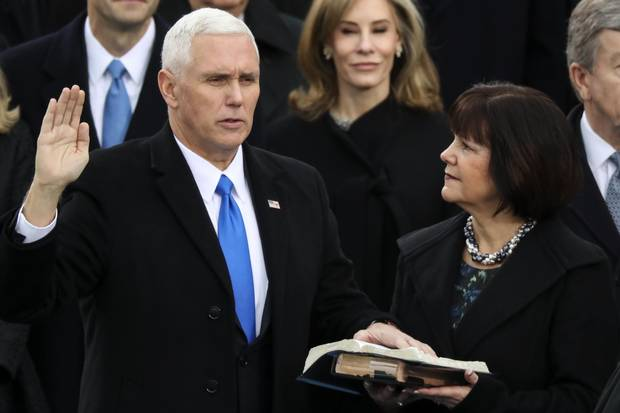 Vice President Mike Pence is sworn in as his wife, Karen, holds the Bible.