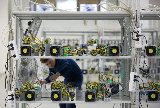 An employee checks power supply units and cooling fans used in cryptocurrency mining machine systems at the SberBit mining 'hotel' in Moscow, Russia, Dec. 9, 2017.