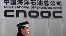 A security officer keeps watch outside the headquarters of China National Offshore Oil Corp (CNOOC), China's top offshore oil producer, in Beijing in this February 19, 2008, file photo. (CLARO CORTES IV/REUTERS)