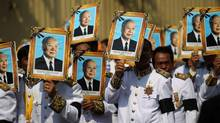 Procession participants shield themselves from the sun with portraits of the late former Cambodian King Norodom Sihanouk in a funeral procession in Phnom Penh, Feb. 1, 2013. (Wong Maye-E/AP)