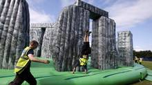 James Carretero, center, of Spain, jokes around as he and other workers install the Sacrilege, a life-sized inflatable replica of Stonehenge, Saturday, July 21, 2012, in Greenwich, London. (Jae C. Hong/AP)