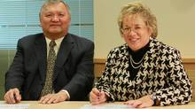 Gitxsan Hereditary Chief Elmer Derrick signs historic equity agreement with Janet Holder, Executive Vice President of Western Access for Enbridge. (Handout/Handout)