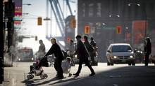 Pedestrians cross W. Georgia St. in Vancouver Tuesday. An average of 18 road users are killed in traffic collisions each year in Vancouver, according to Vancouver Police Department 2006-2011 data. (John Lehmann/The Globe and Mail/John Lehmann/The Globe and Mail)