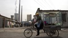 China, the world's largest producer of carbon dioxide, is directly feeling the man-made heat of global warming as scientists link the burning of fossil fuels to one country's rise in its daily temperature spikes. (Andy Wong/Associated Press)