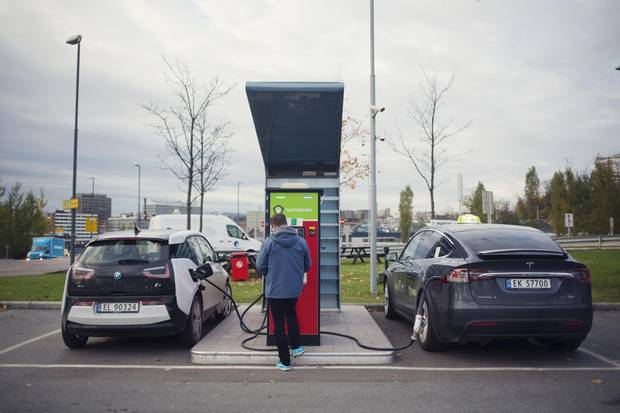 Electric automobiles manufactured by BMG, left, and Tesla sit at an electric vehicle charging station at a Circle K gas station near Oslo. Circle K owner Couche-Tard is using the Nordic country as a testing ground for how to respond to the electric-vehicle boom.