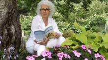 Merilyn Simonds reads in the garden at her home north of Kingston. (Mark Bergin for The Globe and Mail)