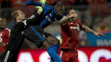 Toronto FC keeper Stefan Frei (left) leaps in as Danny Califf (right) battles with Montreal Impact's Hassoum Camara (centre) during second half Canadian Championship qualifying action in Toronto on Wednesday, April 24, 2013. (Frank Gunn/THE CANADIAN PRESS)