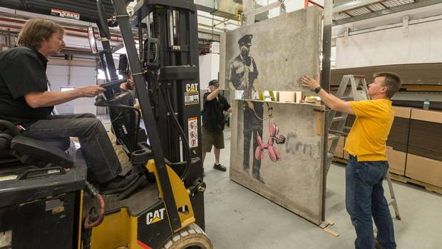 Forklift operator George Dickson, Matt Meagher of Museum Pros, and structural engineer Ira Idzkowski of Torcon Canada, work to reassemble the Banksy piece following its removal from the building at 90 Harbour Street, prior to its demolition.