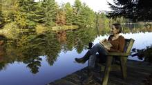 Barbara Reid reads on the canoe dock at her family cottage on Ontario's Severn River. (Ian Crysler)