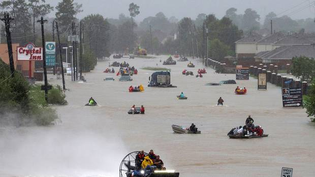 Residents use boats to evacuate flood waters from Tropical Storm Harvey along Tidwell Road east Houston, Texas, U.S. August 28, 2017.