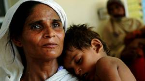 A woman displaced by floods in Pakistan carries her son at a health centre in Muzaffargarh on Aug. 21.