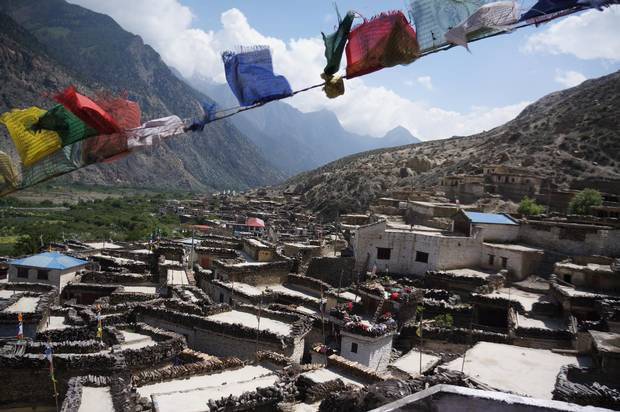 Prayer flags flutter over Marpha, a village known for its traditional flat-roofed homes, apple orchards and apricot brandy.