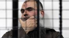The radical al-Qaeda-linked preacher Abu Qatada looks on from behind bars at the Jordanian military court in Amman, Jordan, on June 26, 2014. (RAAD ADAYLEH/ASSOCIATED PRESS)