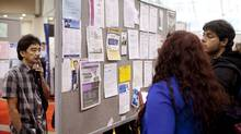 Alex Dagorio, left, looks at the job board during the National Job Fair and Training Expo at the Metro Toronto Convention Centre. Manufacturing employment tumbled to another record low, while in the finance and real estate industry, three-month average job losses are the steepest on record. (Matthew Sherwood for The Globe and Mail/Matthew Sherwood for The Globe and Mail)