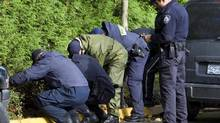 Members of the RCMP search the property surrounding an apartment building where six people died in a mulitple homicide in Surrey, B.C. Wednesday, Oct. 24, 2007. (JONATHAN HAYWARD/THE CANADIAN PRESS)