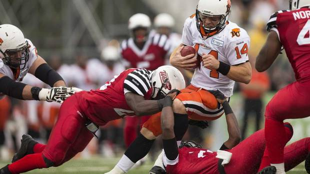 B.C. Lions quarterback Travis Lulay is sacked by Hamilton Tiger-Cats Jamall Johnson (L) and Brandon Isaac during the first half of their CFL football game in Guelph, Ontario, September 7, 2013. (GEOFF ROBINS/REUTERS)