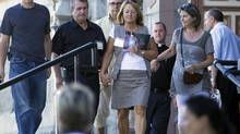 A woman holds a photograph as she walks out of St. Agnes Catholic Church following a silent visit in Lac-Mégantic, Que., on July 11, 2013. According to a priest, this was a silent visit for the families who have lost someone. He said that not a word was spoken inside, and added that it was very important that these be the first families to visit here. (PETER POWER/THE GLOBE AND MAIL)