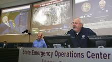 Florida Governor Rick Scott, left, listens to Federal Emergency Management Agency Administrator Craig Fugate speak to workers inside the State Emergency Operations Center in Tallahassee, Fla., on Aug. 27, 2012, as Tropical Storm Isaac churned across the Gulf of Mexico. (PHILIP SEARS/REUTER)