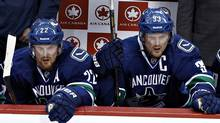 Vancouver Canucks Henrik Sedin and his brother Daniel watch game play against the San Jose Sharks during Game 1 of their NHL Western Conference quarter final hockey playoff in Vancouver, British Columbia May 1, 2013 (Reuters)