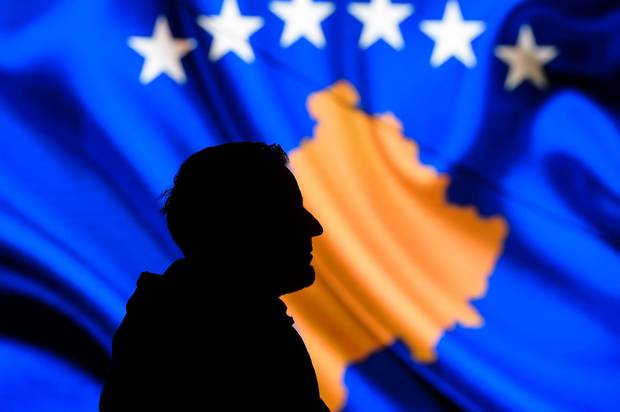 A man is seen in silhouette as he stands in front of a screen displaying the Kosovo flag during a performance by the United States Air Forces in Europe Band in Pristina on February 15, 2018.