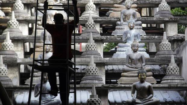 A silhouetted worker climbs a ladder near rows of buddha statues at the Gangaramaya Temple complex in Colombo, Sri Lanka, on Wednesday, July 22, 2015.