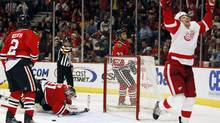 Detroit Red Wings' Brad Stuart (R) scores the game-winning goal in overtime against the Chicago Blackhawks as Duncan Keith, goalie Antti Niemi and Dustin Byfuglien of the Blackhawks look on in overtime of their NHL hockey game in Chicago, April 11, 2010 REUTERS/Jeff Haynes (JEFF HAYNES)