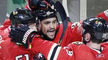 Chicago Blackhawks' Dustin Byfuglien reacts with team mates Jonathan Toews (R) and Brian Campbell to scoring on San Jose Sharks goalie Evgeni Nabokov during the third period in Game 4 of their NHL Western Conference final hockey game in Chicago, May 23, 2010. REUTERS/John Gress (JOHN GRESS)