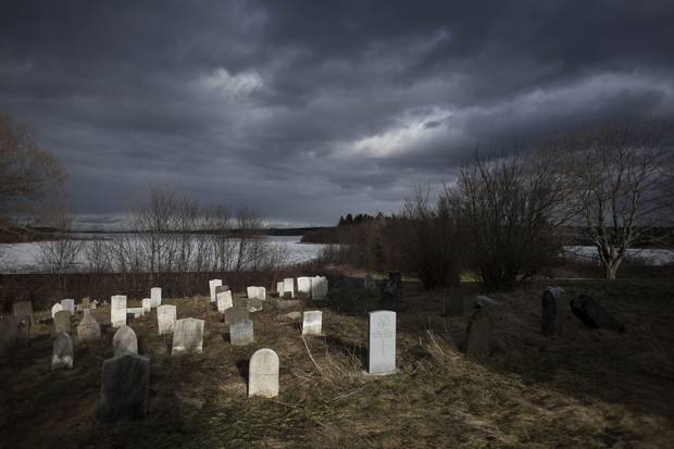 Headstones, including those of other soldiers who served in the armed forces, rest near Church Cove behind St. Peter's Parish in Tracadie, N.S.