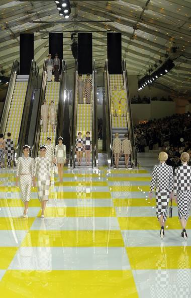 It seemed unlikely that Louis Vuitton could top last season's fully functional steam train that chugged into a tent within the Louvre. But in a way, the mega-brand did exactly that, thanks to artist Daniel Buren, best known for Les Deux Plateaux, the striped columns within the Palais Royal. Here, four escalators appear at the far end of the yellow-checkered runway. (AP)