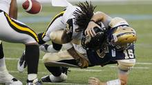 Winnipeg Blue Bombers' quarterback Max Hall (15) fumbles the ball as he is sacked by Hamilton Tiger-Cats' Rico Murray (0) during the first half of their CFL game in Winnipeg Friday, August 16, 2013. (John Woods/THE CANADIAN PRESS)