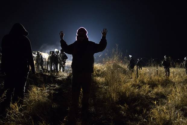 "A demonstrator, or ""water protector,"" meets a police blockade on Highway 1806 near Cannon Ball. Many people were injured when, in sub-zero temperatures, police deployed water cannons, pepper spray, tear gas, rubber bullets and percussion grenades."
