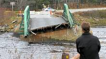 A bystander looks over the Tusket River bridge on Wednesday, November 10, 2010 along Highway 3 in Tusket, Nova Scotia. The structure collapsed from the stain of floodwaters after the area was hit with heavy and wind and rain. Much of Southwest Nova Scotia is dealing with road and bridge closures as rivers and waterways continue to spill their banks. (Mike Dembeck/The Canadian Press/Mike Dembeck/The Canadian Press)