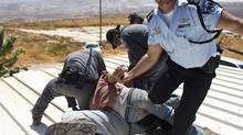 Israeli police scuffle with a Jewish settler as they remove him from a roof on which he barricaded himself in the illegal outpost of Migron, near the West Bank city of Ramallah, after eviction orders were handed to the residents September 2, 2012. (NIR ELIAS/REUTERS)