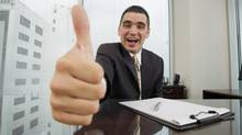 A businessman gives a thumbs-up (Jupiterimages/Getty Images)