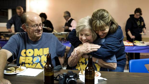 Diane Marson, centre, receives a hug from actress Sharon Wheatley, who plays her in the musical Come From Away, as husband Nick looks on.