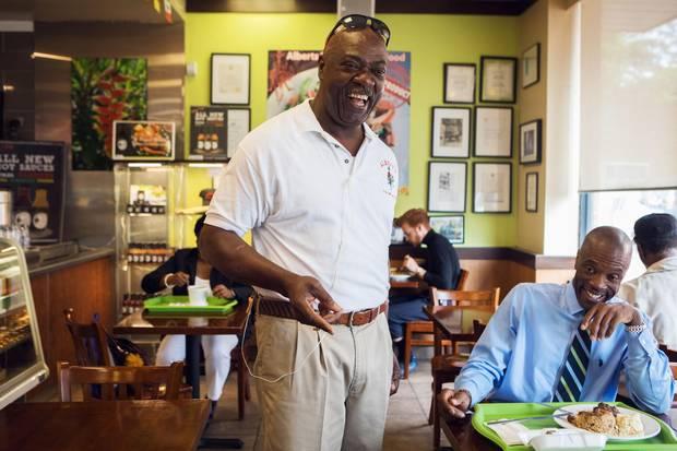 Albert Wiggan speaks with a customer in his restaurant, Albert's Real Jamaican Foods, on Thursday.