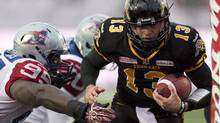 Hamilton Tiger-Cats quarterback Dan LeFevour runs in the game winning touchdown past Montreal Alouettes defensive tackle Moton Hopkins (95) during overtime East Division semifinal CFL action in Guelph, Ont., on Sunday, November 10, 2013. (FRANK GUNN/THE CANADIAN PRESS)