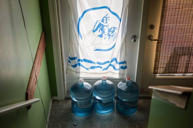 Containers filled with drinking water in the entrance of a home in Fort McKay, Alta. While residents used to drink directly from the nearby Athabasca River, they can now not even consume the treated tap water.